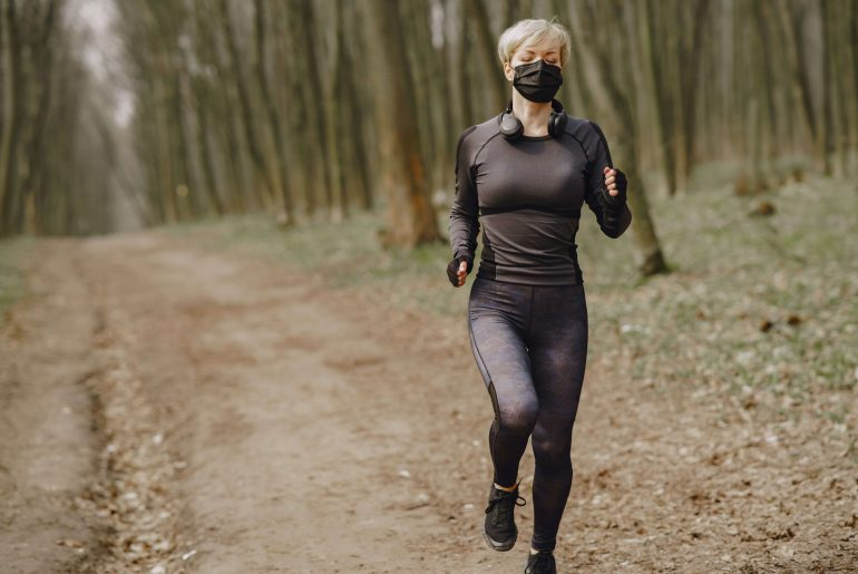 fit-woman-in-sportswear-and-mask-jogging-along-forest-alley